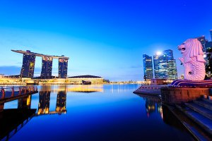The Marina Bay Sands Hotel and the Merlion situated on the edge of the Marina Bay Reservoir, a mythical creature with the head of a lion and the body of a fish, designed by Fraser Brunner and used as a mascot of Singapore.