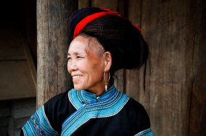 Portrait of a White H'mong hill tribe woman with distinctive big hair and traditional clothing, in Muong Hum market near to Sapa.