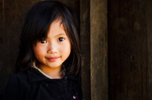 Portrait of a Black Dzao hill tribe child standing in a wooden doorway wearing traditional clothing, located in small village near to Sin Ho.