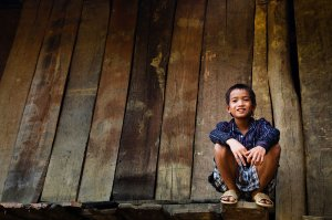Portrait of a Lu hill tribe boy sitting outside his stilted house, located in small village near to Binh Lu.