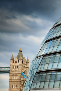 The iconic City Hall building, the home of the Greater London Authority, with Tower Bridge over the River Thames in the background, located in the Southwark Borough of London.
