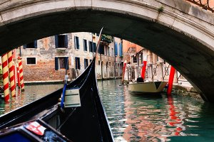 Gondolier taking tourists on gondola boat ride on the narrow canals of the UNESCO World Heritage Site of Venice.
