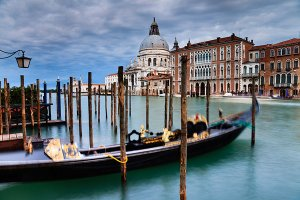 View of the Grand Canal and gondola boats, with the Basilica di Santa Maria della Salute in the background, located in the UNESCO World Heritage Site of Venice.